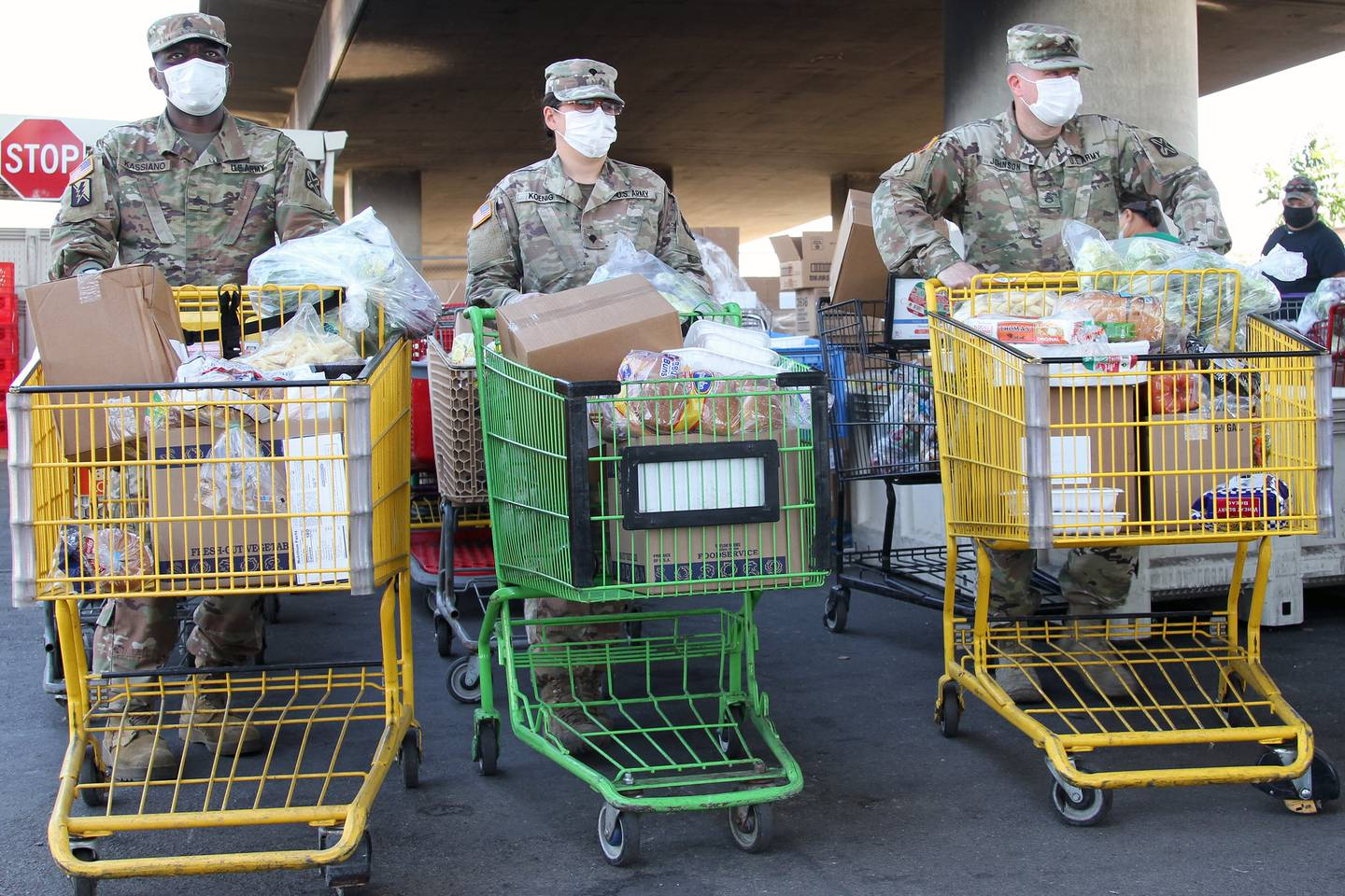 Soldiers with the California National Guard move grocery carts filled with food and await the arrival of recipients on June 26, 2020, at the Stockton/San Joaquin Emergency Food Bank in Stockton, Calif.