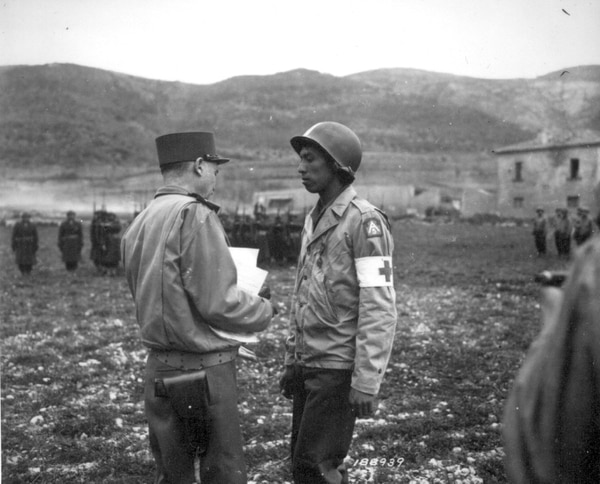 Pvt. Jonathan Hoag is awarded the Croix de Guerre by Gen. Alphonse Juin for courage shown in treating the wounded, even though he, himself, was wounded. Pozzuoli area, Italy, March 21, 1944. (National Archives)