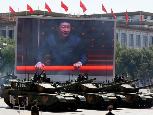 In this Sept. 3, 2015, file photo, Chinese President Xi Jinping is displayed on a screen as Type 99A2 Chinese battle tanks take part in a parade commemorating the 70th anniversary of Japan's surrender during World War II held in front of Tiananmen Gate in Beijing. (Ng Han Guan/AP)