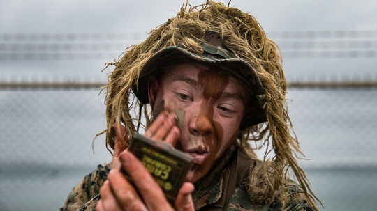 Lance Cpl. Jerren Strong covers his face with camo paint in preparation for a simulated boat raid at Kin Red, Okinawa, Japan, Dec. 16, 2020. (Lance Cpl. Brienna Tuck/Marine Corps)
