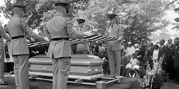 The American flag is held over the coffin of American civil rights activist Medgar Evers during his funeral, on June 20, 1963, in Arlington National Cemetery, in Washington DC, as his wife Myrlie Evers Williams, his daughter and his son look on. (AFP/Getty Images)