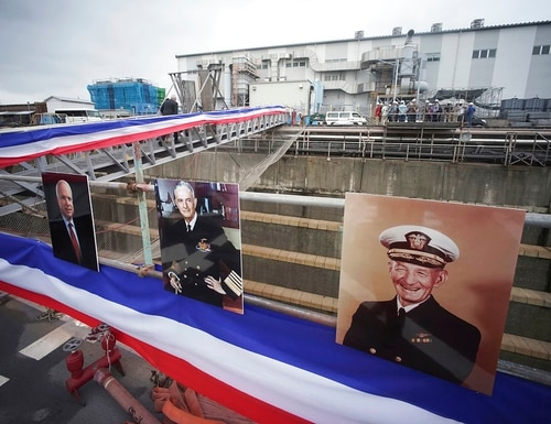 Near the portraits of, from right, John S. McCain, John S. McCain Jr. and Sen. John S. McCain III, Navy Secretary Richard Spencer and his wife Polly Spencer disembark from the USS John S. McCain after a rededication ceremony at the U.S. Naval base in Yokosuka, southwest of Tokyo, Thursday, July 12, 2018. (Eugene Hoshiko/AP)