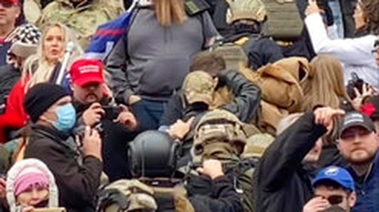 In this Jan. 6, 2021 image from video provided by Robyn Stevens Brody, a line of men wearing helmets and olive drab body armor walk up the marble stairs outside the U.S. Capitol in Washington in an orderly single-file line, each man holding the jacket collar of the man ahead. The formation, known as