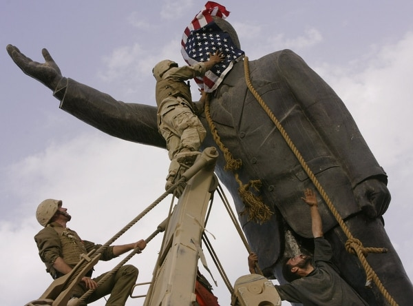 An Iraqi man watches Cpl. Edward Chin of the 3rd Battalion, 4th Marines, cover the face of a statue of Saddam Hussein with an American flag before toppling the statue in downtown in Baghdad, Iraq, April 9, 2003. (Jerome Delay/AP)