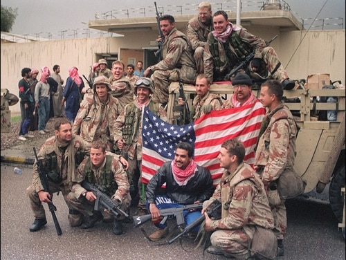 Several members of the U.S. Special forces holding a U.S. flag celebrate their victory over the Iraqi army on Feb. 27, 1991, in Kuwait City. (Christophe Simon/AFP via Getty Images)