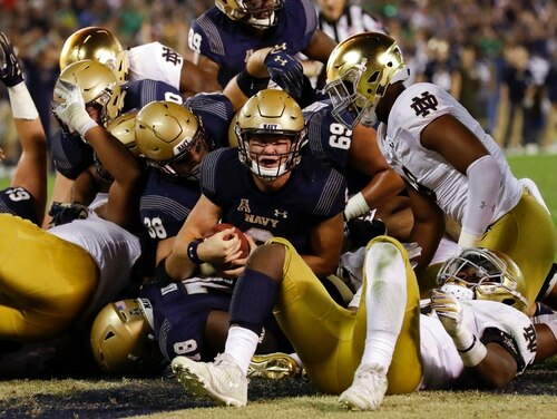 Navy quarterback Zach Abey, center, scores a touchdown against Notre Dame on Saturday in San Diego. (Gregory Bull/AP)