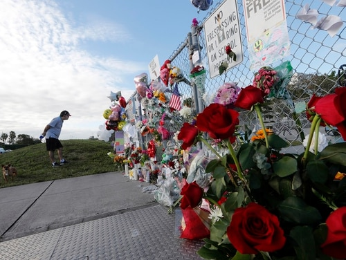 Pablo Gomez, whose wife teaches at the school, visits a makeshift memorial outside of Marjory Stoneman Douglas High School, where 17 students and faculty were killed in a mass shooting on Wednesday in Parkland, Fla. (Gerald Herbert/AP)