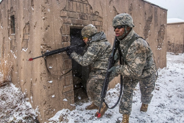 Sgt. Wilfredo S. Rodriguez-Ramos, left, provides cover fire as Pfc. Emery L. Bowens, both with the 328th Military Police Company, New Jersey Army National Guard, crosses between buildings in the military operations in urban terrain training site at Joint Base McGuire-Dix-Lakehurst, N.J., March 20, 2015. (U.S. Air National Guard Photo by Master Sgt. Mark C. Olsen/Released)