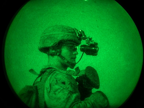 Cpl. Benjamin Harris, a rifleman with 3rd Battalion 7th Marine Regiment attached to Special Purpose Marine Air-Ground Task Force, looks through his night ocular device, scanning the area during a night patrol (Cpl. Gabino Perez/Marine Corps)
