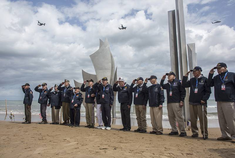 World War II veterans from the United States salute as they pose in front of Les Braves monument at Omaha Beach in Saint-Laurent-sur-Mer, Normandy, France