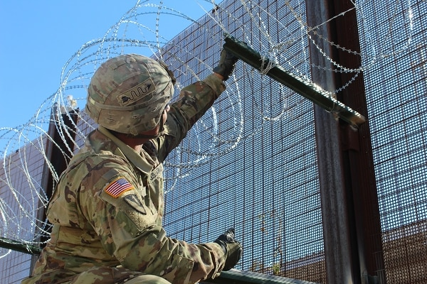 Spc. Pedro Vela, 937th Clearance Company, ties concertina wire to a picket at the Arizona-Mexico border, Nov. 16, 2018. (2nd Lt. Corey Maisch/Army)