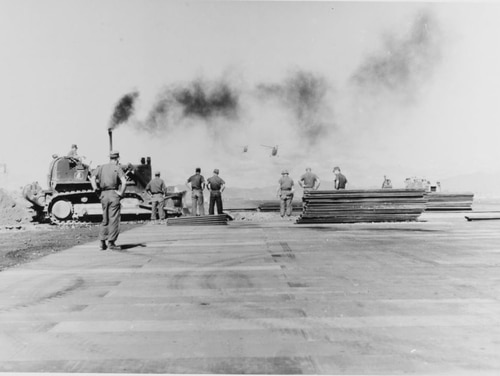 Seabees of the 11th Naval Mobile Construction Battalion lay aluminum matting on a runway damaged by enemy mortar fire at Dong Ha, Quang Tri Province, South Vietnam, 1967. (National Archives)