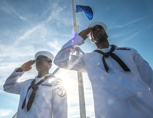 Then-Quartermaster 3rd Class Danavil Mojet, left, and then-Quartermaster 2nd Class Matthew Lewis, on board the aircraft carrier John C Stennis at Naval Station, Norfolk, salute the national ensign after hoisting the Union Jack at morning colors in June 2019. (Staff)