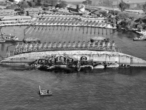 An aerial view of salvage operations on the battleship Oklahoma at Pearl Harbor, Hawaii. The ship capsized during the Japanese attack on Pearl Harbor in 1941. (Navy)