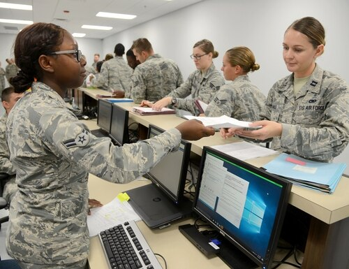 Airman 1st Class Maiesha Buford of the 72nd Aerospace Medicine Squadron gives Capt. Theresa Hall her medical file at Tinker Air Force Base in Oklahoma in October 2017. (Kelly White/Air Force)