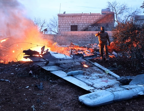 A picture taken on Feb. 3, 2018, shows a rebel fighter taking a picture of a downed Sukhoi-25 fighter jet in Syria's northwest province of Idlib. (Omar Haj Kadour/AFP/Getty Images)