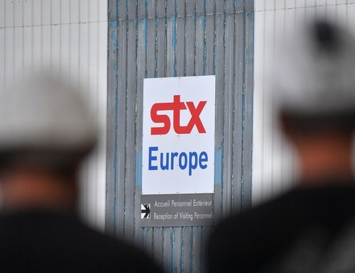 Workers pass the STX shipyards on Sept. 27, 2017, in Saint-Nazaire, western France, a few hours before Rome and Paris announced an agreement about the shipyards during a French-Italian summit. (Loic Venance/AFP via Getty Images)