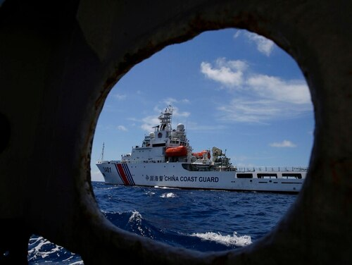 In this 2014 photo, a Chinese Coast Guard ship attempts to block a Philippine government vessel as the latter tries to enter Second Thomas Shoal to relieve Philippine troops and resupply provisions. (Bullit Marquez/AP)