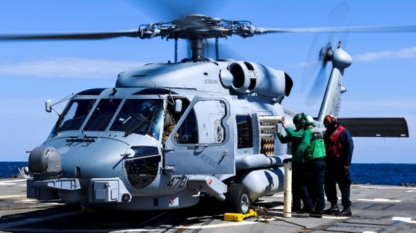 Sailors load sonobuoys onto an MH-60R Sea Hawk helicopter on the flight deck of the Arleigh Burke-class guided-missile destroyer USS Oscar Austin (DDG 79) during flight operations May 10, 2017. (US Navy/Sean Spratt)