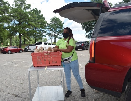 Tiara Edwards loads groceries in the vehicle of a customer who has ordered items online from the commissary at Fort Lee, Va. (Rick Brink/Defense Commissary Agency)