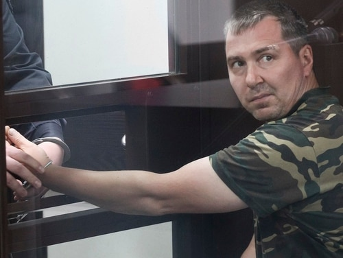 Alexander Popov, a man who was arrested on suspicion of murder sits behind the glass in a courtroom in the city of Gorodets, 36 miles northwest of Nizhny Novgorod, Russia, Sunday, June 20, 2021. (Roman Yarovitsyn/AP)