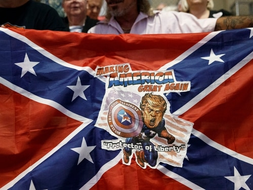 A man holds a Confederate flag with a depiction of then presidential candidate Donald Trump during a campaign rally in Florida on Nov. 3, 2016. (Evan Vucci/AP)