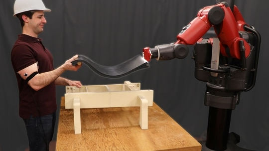 Using signals from a sensor placed on the human's arm, the robot can lift at the same time and intensity of the human, and then release the object when the human's muscle relaxes. (Joseph DelPreto / MIT CSAIL)