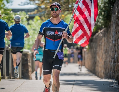 Mike Ergo carrying the flag for a fallen Marine at IRONMAN Santa Rosa in 2019. (Mike Ergo)