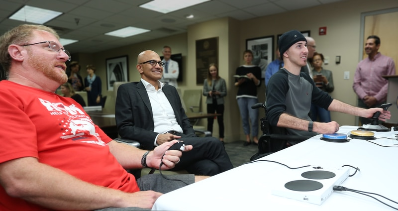 Retired Master Gunnery Sgt. Roger Brannon (Left) tests out the Xbox Adaptive Controller with Microsoft CEO Satya Nadella (Center) and fellow veteran Matthew Wade (Right). (Courtesy U.S. Department of Veterans Affairs)