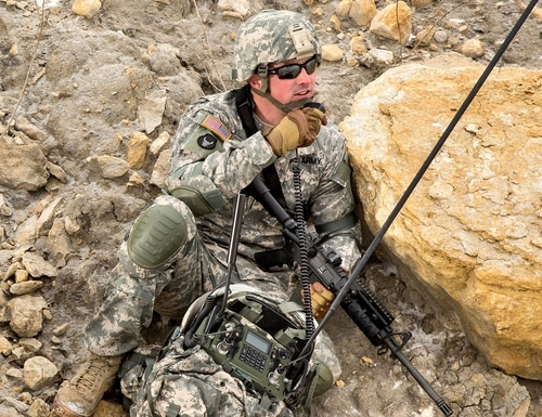 A soldier uses the Manpack Radio, which provides beyond line-of-sight connectivity through multiple waveforms, enabling communication despite obstacles such as buildings and difficult terrain. (Courtesy Rockwell Collins)