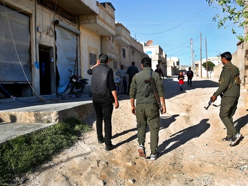 Members of the Kurdish internal security forces pass near damaged shops at the scene where an explosion on March 29 hit U.S.-led coalition vehicles, killing two soldiers - an American and a Briton - in Manbij town, north Syria, Saturday, March 31, 2018. (Hussein Malla/AP)