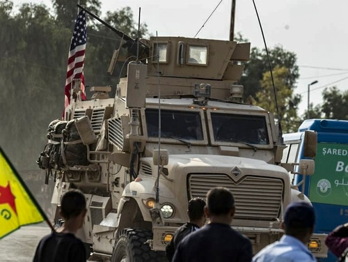Syrian Kurds, one of them carrying a Kurdish YPG (People's Protection Units) flag, watch as a U.S. military vehicle drives on a road after U.S. forces pulled out of their base in the northern Syrian town of Tal Tamr, on Oct. 20, 2019. (Delil Souleiman/AFP via Getty Images)