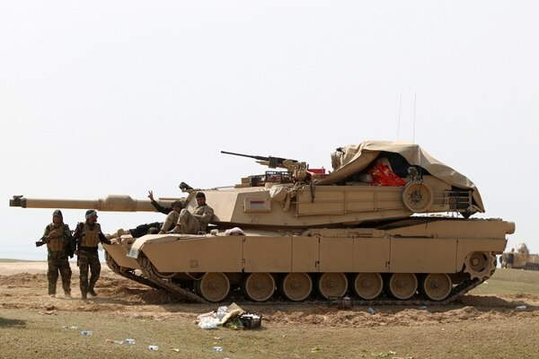 Iraqi Shiite fighters from the Popular Mobilisation units sit on a tank as they hold a position near Lake Thar Thar in the desert West of the city of Samarra, on March 4, 2016 during a military operation aimed at retaking areas from the Islamic State (IS) jihadist group. Counter-terrorism forces, soldiers, police and allied paramilitaries are taking part in an operation launched , which is backed by artillery and both Iraqi and US-led coalition aircraft, aimed at retaking areas north of Baghdad, according to the Joint Operations Command. An Iraqi army colonel said that more than 7,000 security personnel would take part in the operation, which the operations command said aims to retake areas west of the city of Samarra. / AFP / AHMAD AL-RUBAYE (Photo credit should read AHMAD AL-RUBAYE/AFP/Getty Images)