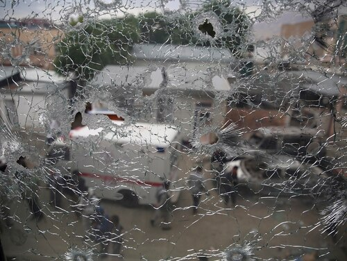 Afghan security security officers are seen through the shattered window of a maternity hospital after gunmen attacked, in Kabul, Afghanistan, Tuesday, May 12, 2020. (Rahmat Gul/AP)