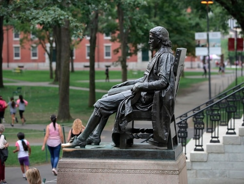 In this Aug. 13 photo, the statue of John Harvard sits in Harvard Yard at Harvard University in Cambridge, Mass. Federal prosecutors on Tuesday charged Harvard University professor Charles Leiber, chair of the department of chemistry and chemical biology, with lying to officials about his involvement with a Chinese government-run recruitment program through which he received tens of thousands of dollars. (Charles Krupa/AP)