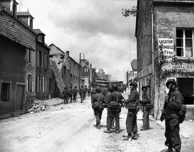 American paratroops patrol in Sainte-Mere-Eglise, France, during World War II.