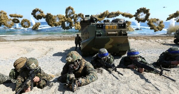 U.S. Marines, left, and South Korean marines, wearing blue headbands on their helmets, take positions after landing on the beach during the joint military combined amphibious exercise Ssangyong on March 12, 2016. (Kim Jun-bum/Yonhap via AP)