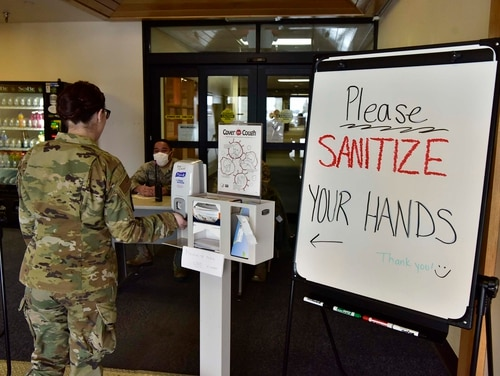 An airman sanitizes her hands on Eielson Air Force Base, Alaska, March 20, 2020. The 354th MDG has taken extra precautions to help stop the spread of the novel coronavirus including implementing a checkpoint at the front entrance of the clinic. (Senior Airman Beaux Hebert/Air Force)
