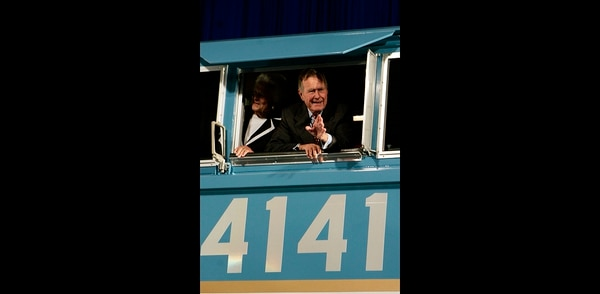 In this Oct. 18, 2005, file photo, former President George H.W. Bush and his wife Barbara wave out the window of a new locomotive numbered 4141 in honor of the 41st president at Texas A&M University in College Station, Texas. (Pat Sullivan/AP)