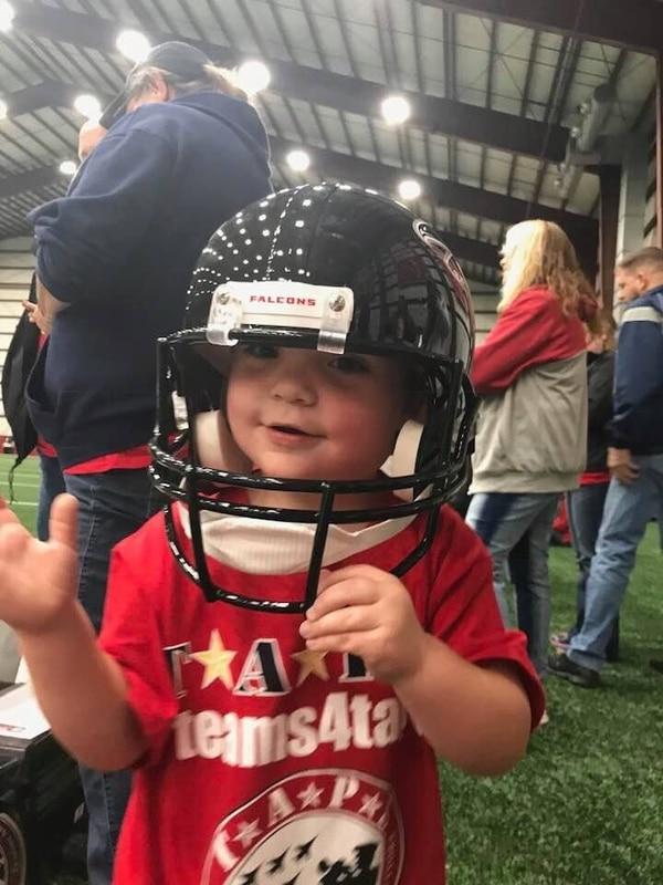 Cooper Dean, 3, wears a replica helmet at the Atlanta Falcons training facility. (Tragedy Assistance Program for Survivors)