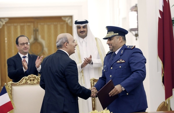 Eric Trappier, front left, head of Dassault Aviation, shakes hands with Qatari Gen. Ahmad Al-Malki after signing an agreement for Rafale fighters at the Diwan Palace in Doha on May 4, 2015. (Christophe Ena/AFP via Getty Images)