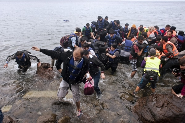 People wade through the water after getting off an inflatable boat onto the shore as migrants and refugees arrive under the rain on Sykamia beach, west of the port of Mytilene, on the Greek island of Lesbos after crossing the Aegean sea from Turkey on September 23, 2015. EU ministers neared a compromise on plans to relocate 120,000 refugees at emergency talks despite deep divisions over how to handle Europe's worst migration crisis since World War II. AFP PHOTO / IAKOVOS HATZISTAVROU (Photo credit should read IAKOVOS HATZISTAVROU/AFP/Getty Images)
