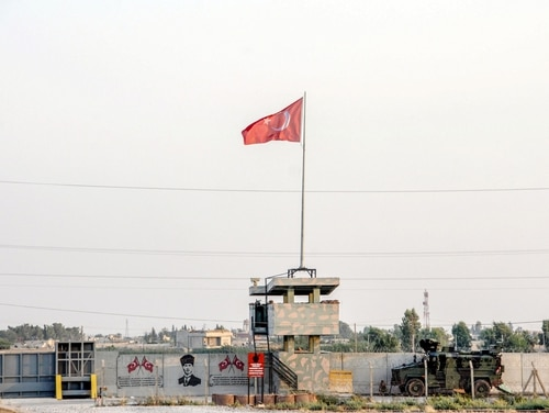 A Turkish military truck patrols next to a Turkish flag hoisted at the border with Syria on Aug. 14, 2019, in Akcakale, in Sanliurfa, southeastern Turkey. (DHA/AFP via Getty Images)