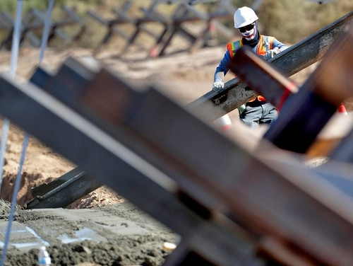 A government contractor, surrounded by existing Normandy barriers that separate Mexico and the United States, pours a concrete footer in preparation for a section of Pentagon-funded border wall along the Colorado River, Tuesday, Sept. 10, 2019 in Yuma, Ariz. (Matt York/AP)