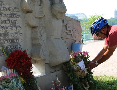 Pham Van Khanh, a 62-year-old retiree, lays flowers at the monument to Sen. John McCain in Hanoi, Vietnam, Monday, Aug. 27, 2018. The monument was erected by Vietnamese authority to mark the day when McCain's plane was shot down in 1967. Vietnam has been paying respects to McCain, who died on Saturday, Aug. 25. (Tran Van Minh/AP)