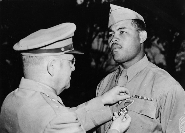U.S. heavyweight boxer Joe Louis (1914-1981), right, is presented with the Legion of Merit medal by Maj. Gen. Clarence H Kells during a Sept. 28, 1945, ceremony at Port Hamilton. (Keystone/Getty Images)