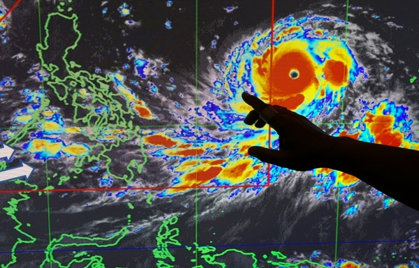 Filipino forecaster Meno Mendoza traces the trajectory of Typhoon Mangkhut, locally named