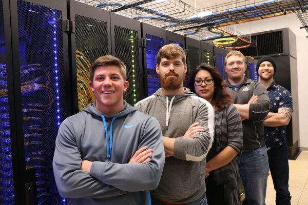 Dakota State University students taking a cybersecurity course pose in the school's academic server classroom. Pictured, from left, are Army National Guardsman Brodie Frederiksen, Army veteran Logan Sampson, Army veteran Jazmin Bautista, Marine veteran Jacob Schaefers, and South Dakota National Guardsman John Patterson. (Provided by Dakota State University)
