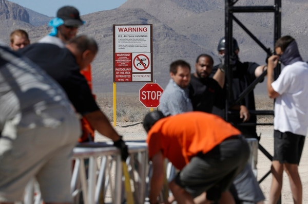 In this Wednesday, Sept. 18, 2019, photo, workers erect a stage near a replica Area 51 gate sign at the Alien Research Center in Hiko, Nev. (John Locher/AP)