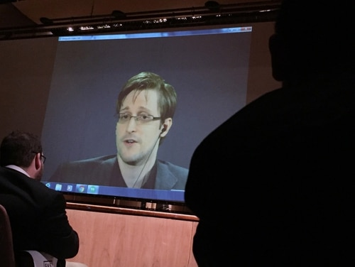 Former National Security Agency contractor Edward Snowden, center speaks via video conference to people in the Johns Hopkins University auditorium, Wednesday, Feb. 17, 2016, in Baltimore. Hopkins students spent months arranging the live video conference Wednesday night with Snowden, according to the Baltimore Sun. (AP Photo/Juliet Linderman)